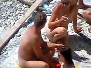 Two couples fool around on the beach