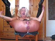 Mature in shiny boots has her ass toyed