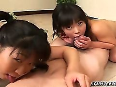 Two cute innoncent Japanese teens playing with a cock